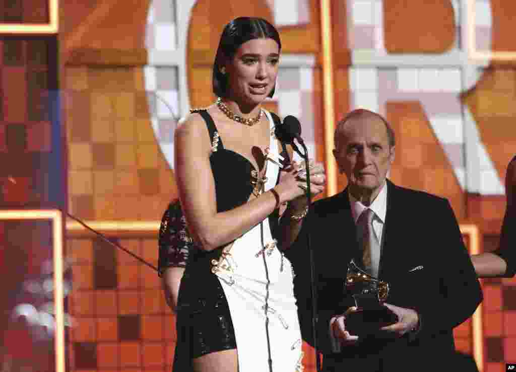Dua Lipa accepts the award for best new artist at the 61st annual Grammy Awards, Feb. 10, 2019, in Los Angeles. Looking on at right is presenter Bob Newhart.