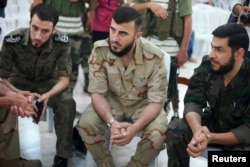 FILE - Zahran Alloush, center, commander of Army of Islam, sits during a conference in the town of Douma, eastern Ghouta in Damascus, Syria, Aug. 27, 2014.