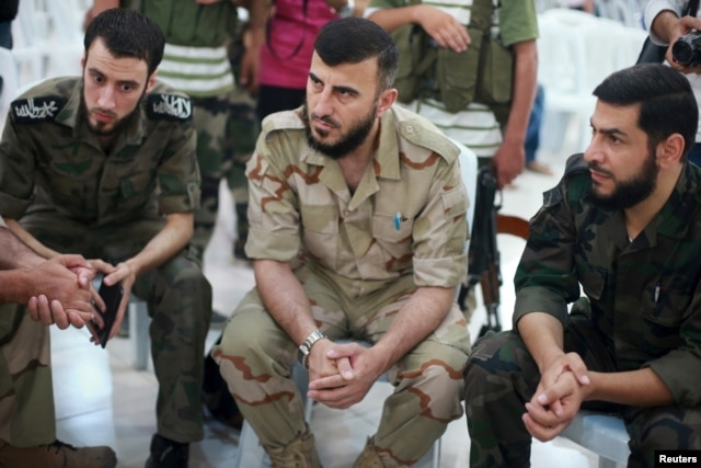 Zahran Alloush, center, commander of Army of Islam, sits during a conference in the town of Douma, eastern Ghouta in Damascus, Syria, Aug. 27, 2014.