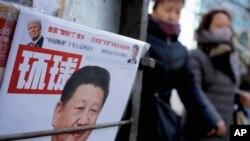 2 medam kap mache bò kote yon ansèy ki genyen foto Prezidan Lachin lan, Xi Jinping, ak foto Prezidan Ameriken, Donald Trump, nan Peken 9 fevriye, 2017. (Foto: AP/Andy Wong)
