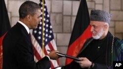 El presidente Barack Obama entrega al presidente afgano Hamid Karzai el histórico acuerdo estratégico firmado por ambos mandatarios.