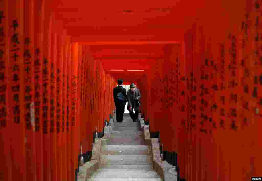 Visitors wearing protective face masks walk through red-colored wooden torii gates at a shrine in Tokyo, Japan.