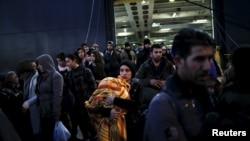 Para pengungsi dan migran menaiki kapal ferry Nissos Rodos di pelabuhan Piraeus, dekat Athena, Yunani, 13 Januari 2016.