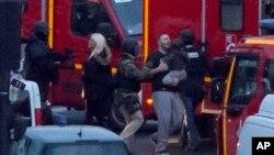 프랑스 경찰이 9일 파리 시내에서 벌어진 인질극을 진압한 가운데, 인질로 붙잡혔던 남성과 아이가 경관들의 도움을 받아 구급차에 오르고 있다.