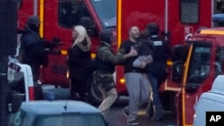 A security officer directs freed hostages to safety after police stormed a kosher market to end the situation in Paris, Jan. 9, 2015.
