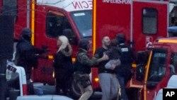 在警察冲进巴黎一家被劫持的犹太超市后,一名保安人员把被解救的人质引向安全地点。(2015年1月9日)