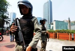 FILE - Indonesian anti-terror policemen hold their rifles as they stand guard at the business district in Jakarta.