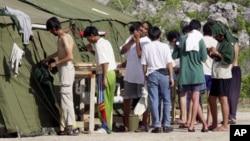 Des migrants se préparent le matin, dans le camp de réfugiés situé sir l'île australienne de Nauru, le 21 septembre 2001.