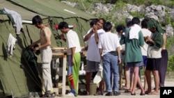 Des hommes se rasent, se brossent les dents et se préparent pour la journée dans un camp de réfugiés sur l'île de Nauru, le 21 septembre 2001.