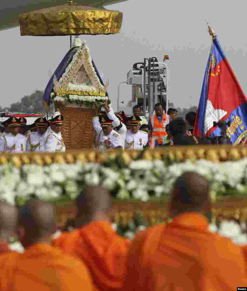Cambodian royal officers carry the coffin of former king Norodom Sihanouk during its arrival at Phnom Penh international airport October 17, 2012.