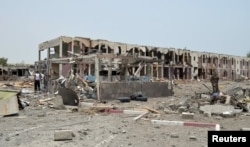 FILE - Damaged houses are seen one day after a Saudi-led air strike hit them in Yemen's western city of Mokha, July 26, 2015.