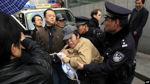 A man, center, is detained by police officers near the planned protest site is located at in Shanghai, China, February 27, 2011