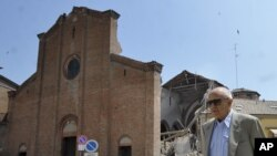 A man walks in front of a collapsed church in Mirandola, northern Italy, May 29, 2012.
