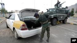 Cảnh sát Yemen khám xét một chiếc xe tại chốt kiểm soát gần Đại sứ quán Mỹ ở Sana'a.