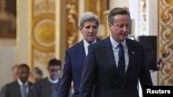 PM Inggris David Cameron, diikuti Menlu AS John Kerry, tiba di lokasi penyelenggaraan KTT Anti Korupsi di London, Inggris (12/5).