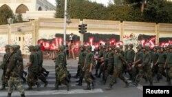 当反穆尔西抗议这2012年12月9日在埃及开罗总统府外面墙上涂鸦的时候,士兵列队行进