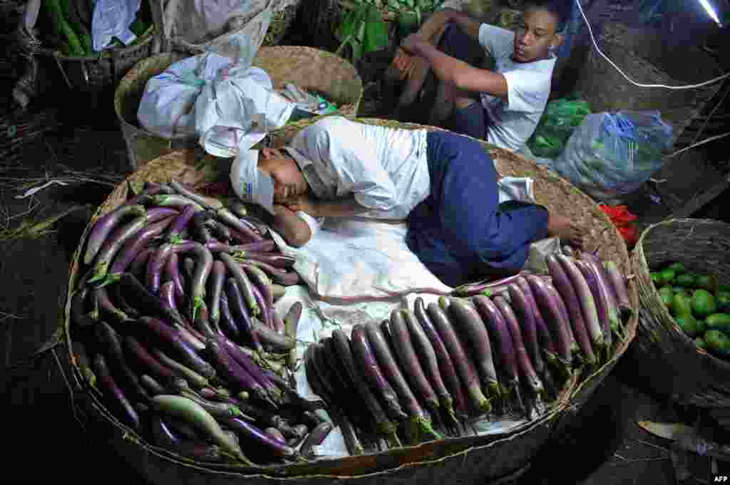 A man rests in a basket at a night market in Rangoon, Burma, Apr. 10, 2013.