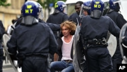 Police in riot gear drag a man along a street in Hackney, east London August 8, 2011