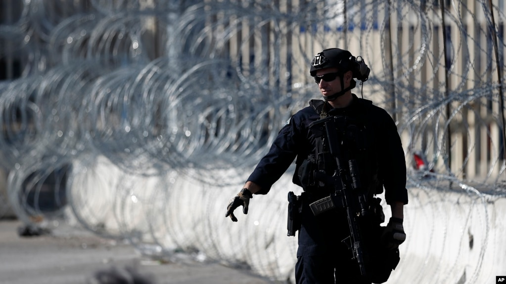 During a training drill, a Customs and Border Protection official stops the flow of northbound traffic at entrance to the San Ysidro port of entry, Jan. 10, 2019, seen from Tijuana, Mexico.