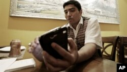 Bigyan Bhandari, a 28-year-old Nepali who works at a Nepalese restaurant run by K.P. Sitoula, uses his smartphone to call his family members in Kathmandu during an interview in Seoul, South Korea, April 27, 2015.
