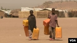 Children trek long distances to fetch water, near Minawao refugee camp in northern Cameroon, Feb. 9 2018. (M. Kindzeka/VOA)