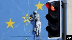 A view of the Banksy Brexit mural of a man chipping away at the EU flag in Dover, England, Tuesday, Dec. 11, 2018.
