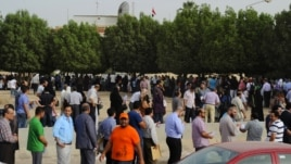 Egyptian nationals living in Kuwait stand in line at the entrance of the Egyptian Embassy before voting in Egypt's presidential elections, in Bnaid al-Gar, Kuwait, May 16, 2012.
