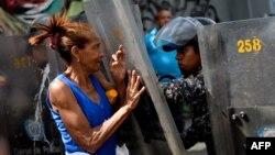 Seorang demonstran bentrok dengan polisi anti huru-hara dalam unjuk rasa di Caracas, Kamis (28/12).