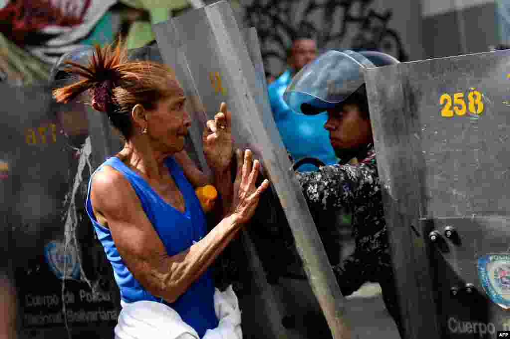 A woman confronts riot police during a protest against the shortage of food, amid Fuerzas Armadas avenue in Caracas.