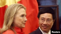 Vietnam's Foreign Minister Pham Binh Minh (R) and U.S. Secretary of State Hillary Clinton in Hanoi, July 10, 2012. Secretary Clinton has stressed repeatedly that significant improvement is needed to build closer relations.