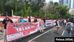Sejumlah kelompok masyarakat di Surabaya membentangkan spanduk tolak FPI di depan Gedung Negara Grahadi (Foto: VOA/Petrus Riski).
