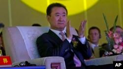 FILE - Wanda Chairman Wang Jianlin applauds in front of the logo for Dalian Wanda Group during an event at a hotel in Beijing, China, June 19, 2013.