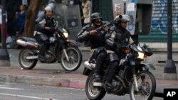 Policías atacan a manifestantes opositores en Caracas, el jueves durante al aniversario del sangriento movimiento de protesta del año pasado.