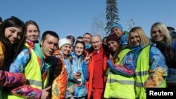 Russian President Vladimir Putin poses for a photograph with volunteers during the Olympic Winter Games in Sochi Feb. 16, 2014.