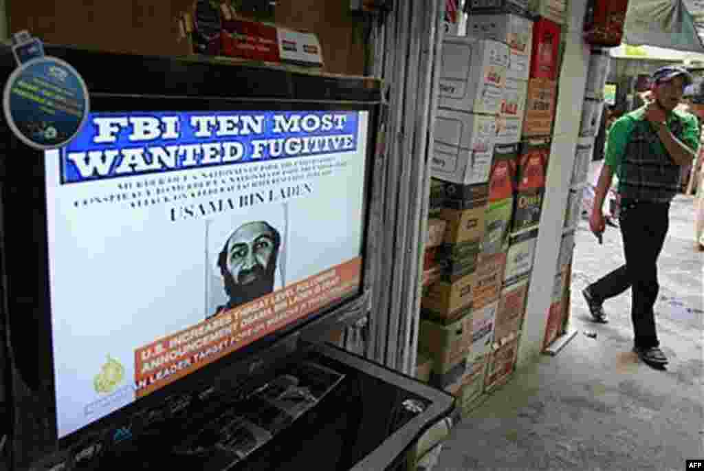 An Afghan youth walks past by a television announcing the death of Al-Qaida leader Osama bin Laden at a market in Kabul, Afghanistan, May 2, 2011 (AP)