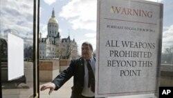 2013年4月3日,一名安全警卫看守康涅狄克州议会的入口,入门的玻璃上贴了一张禁止携带枪支的警告文字。
