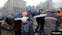 在基辅独立广场,反政府抗议者用担架抬走一名受伤者。(2014年2月20日)