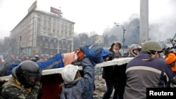Demonstran anti-pemerintah di Ukraina menggotong seorang pria yang terluka dalam protes di Alun-alun Kyiv (20/2).