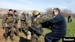 A Ukrainian soldier clashes with a pro-Russia protester in the field near Kramatorsk, in eastern Ukraine April 16, 2014. Ukrainian forces tightened their grip on the eastern town of Kramatorsk on Wednesday after securing control over an airfield from pro-