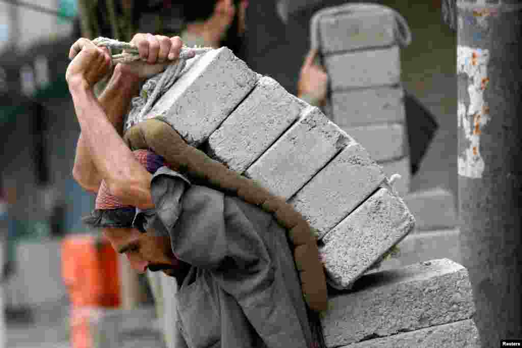 A laborer carries bricks on his back at a construction site in Karachi, Pakistan.
