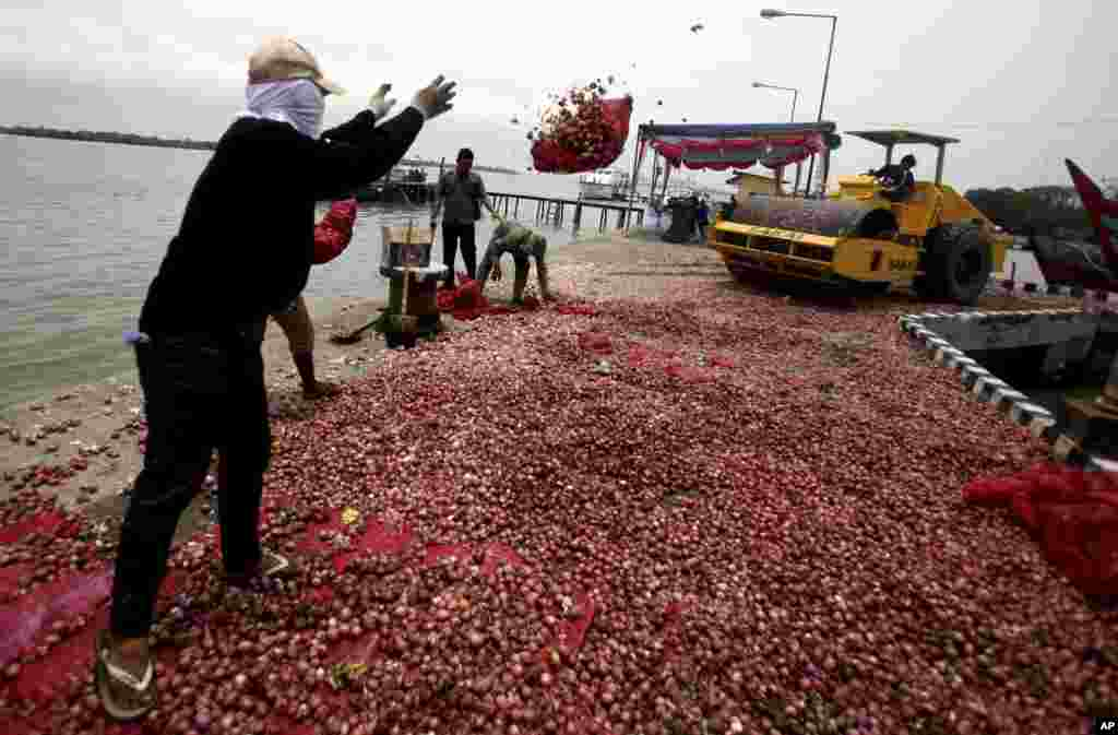 A worker throws a sack of shallots to be crushed by a steamroller at a customs base in Belawan, North Sumatra, Indonesia. Nine tons (19,842 lbs) of shallots and garlic illegally imported from Malaysia were destroyed in the event.
