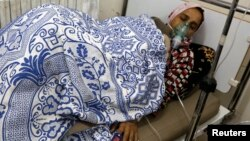 FILE - A woman, affected by what activists say was a gas attack, receives treatment inside a makeshift hospital in Kfar Zeita village in the central province of Hama May 22, 2014.