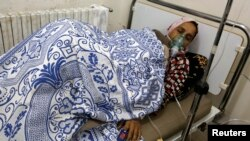 Một phụ nữ bị ảnh hưởng một cuộc tấn công khí ga, theo lời các nhà hoạt động, đang được điều trị tại một bệnh viện ở làng Kfar Zeita, tỉnh Hama, 22/5/2014.