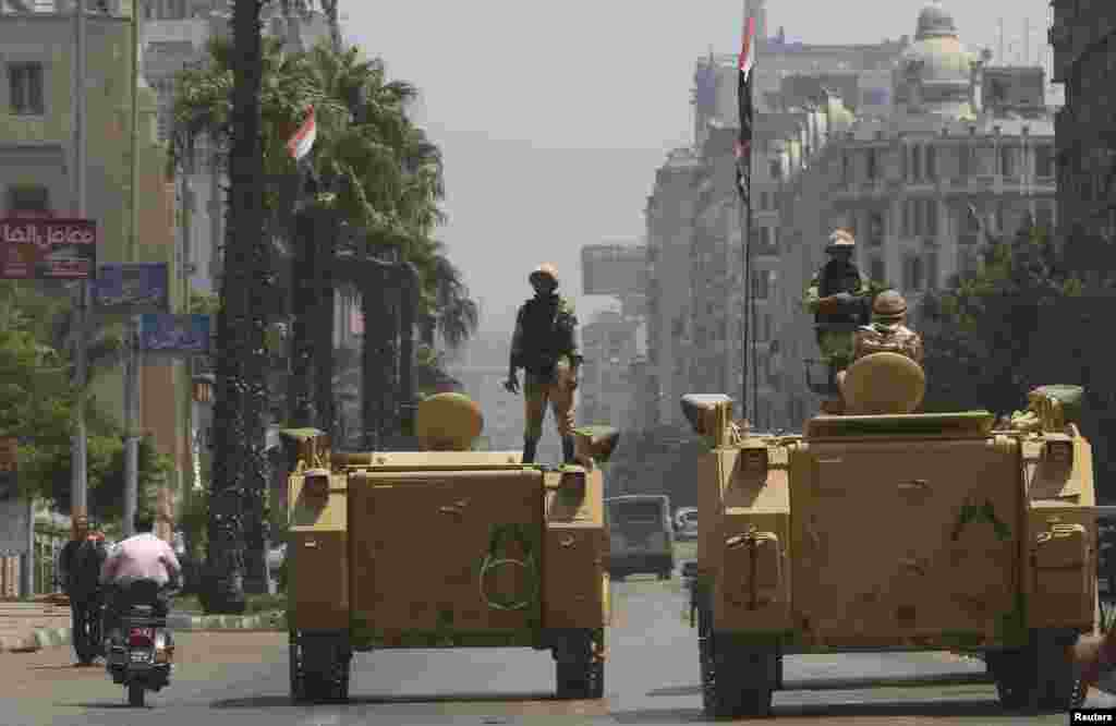 A soldier holds his weapon as he stands on an armored personnel carrier positioned outside the state-run television station in Cairo, August 16, 2013.