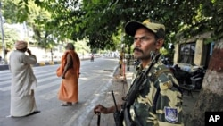 An Indian paramilitary soldier stands guard as Hindu holy men wait outside the Lucknow High Court before the Ayodhya verdict in Lucknow, India, 30 Sept. 2010