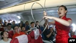 中国东方航空公司的空姐在客机上为乘客表演助兴(2007年9月26日)。