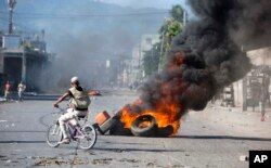 A man rides a bicycle past tires set afire by protesters demanding to know how Petrocaribe funds have been used by the current and past administrations, in Port-au-Prince, Haiti, Oct. 17, 2018.