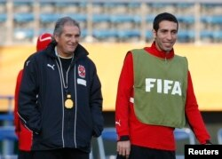 FILE - Head coach Manuel Jose de Jesus and Egypt's football star Mohamed Aboutrika take part in a practice session for the FIFA Club World Cup in Tokyo, Dec. 12, 2008.