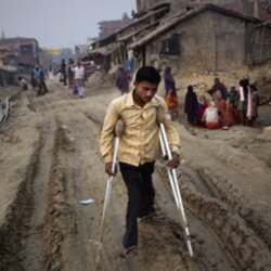 A man with polio in the village of Kosi in India