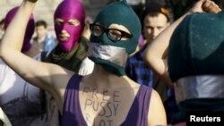 """Aktivisti s maskama pružaju podršku bendu """"Pusi rajot"""" na demostracijama u Varšavi"""